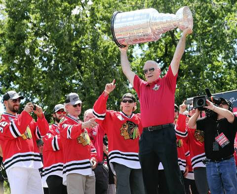 Chicago Blackhawks head coach Joel Quenneville hoists the Cup at the rally.