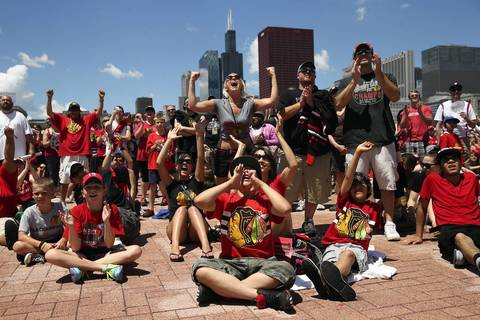 Fans cheer while watching the Chicago Blackhawks' celebration on a video screen near Buckingham Fountain.
