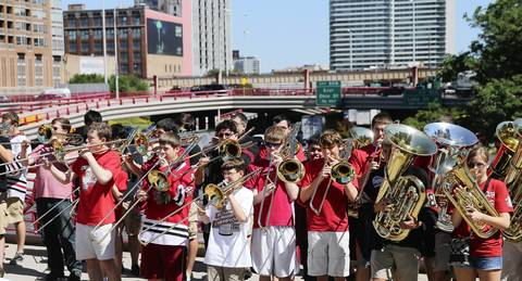 A brass band plays as the parade crosses over the freeway.