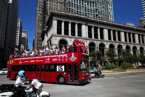 A bus carrying members of the Blackhawks passes the Cultural Center as it turns onto Michigan Avenue.