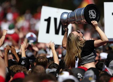 A fan hoists a replica Stanley Cup as people wait for the arrival of the team.