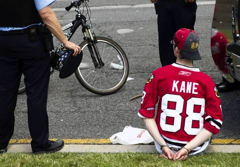 A fan in a Patrick Kane jersey sits handcuffed on the curb after the rally.