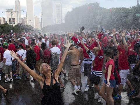 Fans rejoice at a spray mist set up by fire officials after the downtown parade and rally.