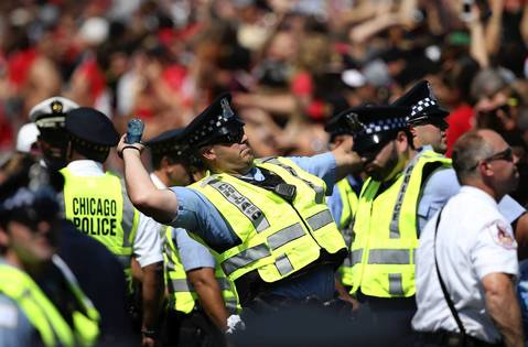 A Chicago police officer throws a bottle of water into the crowd as fans wait for the arrival of the Stanley Cup champion Chicago Blackhawks in Grant Park.