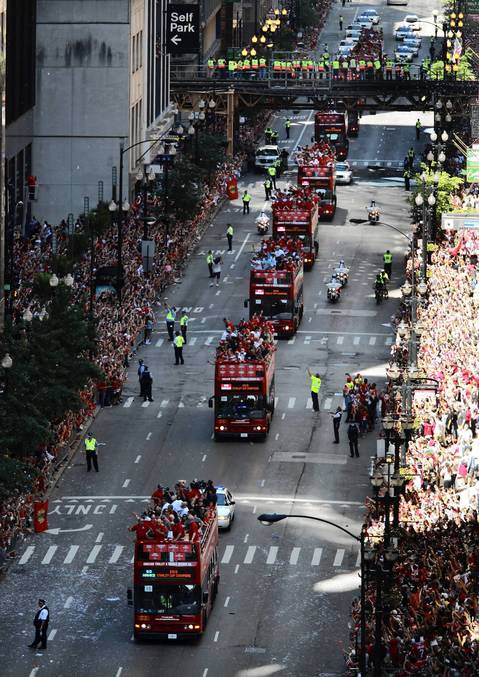 Thousands of fans celebrate and cheer on the Chicago Blackhawks as they make their way down Washington Street during the parade in downtown Chicago.