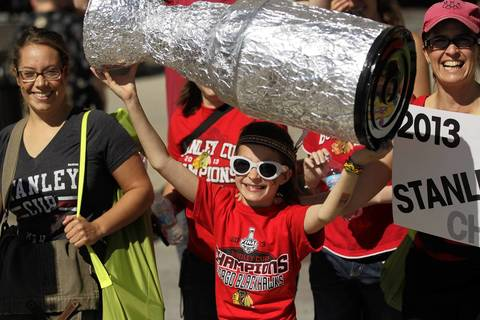 A fan at Michigan Avenue and Congress Parkway holds up her own Stanley Cup.