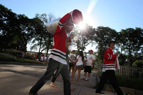 A fan carries his own Stanley Cup to the Blackhawks rally in Chicago.