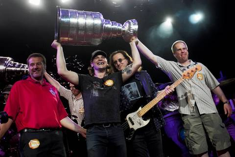 Daniel Carcillo carries the Stanley Cup on stage with members of Rush at the First Midwest Bank Amphitheatre on Friday.