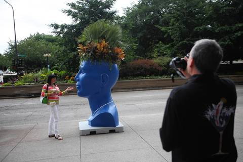 A passer-by has her picture taken with a head planter.