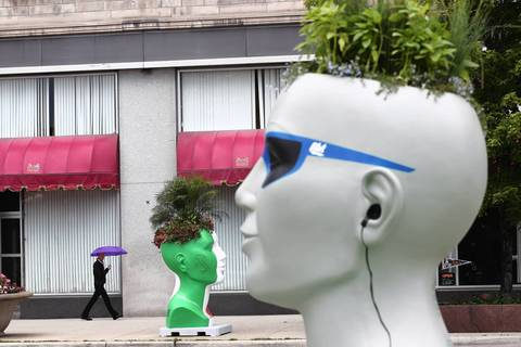 A head planter is painted with earphones and sunglasses. Each planter is sponsored by an area business.
