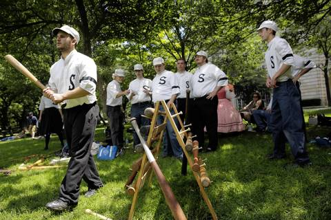 """Chris """"Ouzo"""" Conis, left, heads to the """"disk"""" for the Salmon Base Ball Club of Chicago as they take on the Union Base Ball Club of Minnesota in a 1858 rules Vintage Base Ball Association match in Lincoln Park near the Chicago History Museum. Batters are called strikers."""