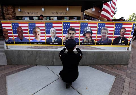 San Diego firefighter Robert Bunsoldat takes a picture of each of the Prescott Fire Department's Granite Mountain Hotshots at their memorial in Prescott Valley, Arizona. Nineteen firefighers lost their lives in battling the Yarnell Hill Fire on June 30.