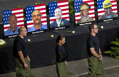 Former Granite Mountain Hotshot firefighters walk past photos of their fallen comrades during the memorial service.