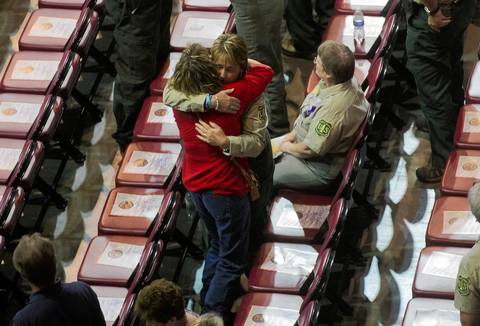 A Prescott National Forrest worker gets a hug from a woman before the memorial service.