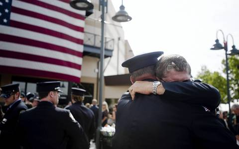 Chaplain Bob Ossler, right, hugs people at the memorial service.