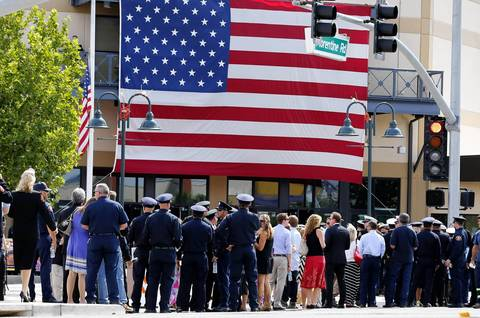 Firefighters, family and emergency personnel arrive at the memorial.