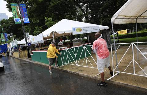 Workers set up fencing in the rain.