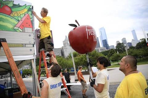 Workers attach a large apple to the Dominick's booth.