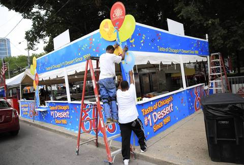 Andre Turner, left, and his brother Chico Turner erect the Eli's Cheesecake booth.