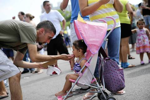 Moises Otero shares a taste of empanada with his two-year-old daughter Lizzie Otero.