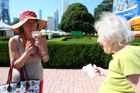 Mary Ann Bulanda, left, eats her second rainbow cone after dropping the first. She and Judy Clasen, right, have been best friends for 18 years and always come to the Taste of Chicago.