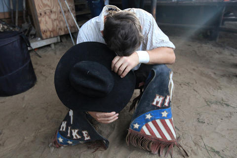 A cowboy prays prior to the Kissimmee Sports Arena Rodeo on Saturday, July 13, 2013. (Megan May/Orlando Sentinel)