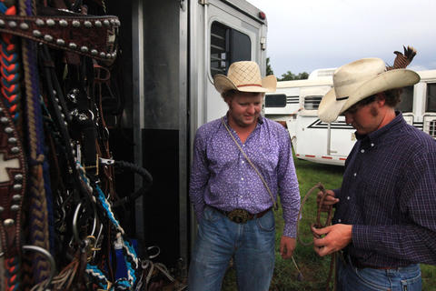 Jarrod Sparks, left, and Jake Anuez grab tack from their trailer prior to the Kissimmee Sports Arena Rodeo on Saturday, July 13, 2013. (Megan May/Orlando Sentinel)