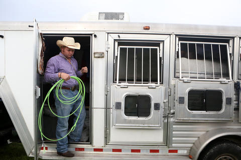 Jarrod Sparks grabs a rope from his trailer prior to the Kissimmee Sports Arena Rodeo on Saturday, July 13, 2013. (Megan May/Orlando Sentinel)