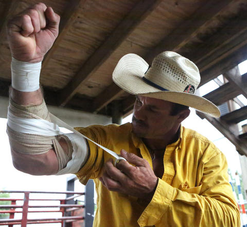 Chris Dillard wraps his arm before bull riding at the Kissimmee Sports Arena Rodeo on Saturday, July 13, 2013. (Megan May/Orlando Sentinel)