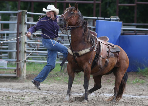 Jake Anuez jumps off his horse to tie down a calf during a roping event at the Kissimmee Sports Arena Rodeo on Saturday, July 13, 2013. (Megan May\Orlando Sentinel)