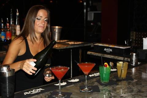 Bar manager Nicole Ward tops off the La Grenada martini with a splash of champagne.