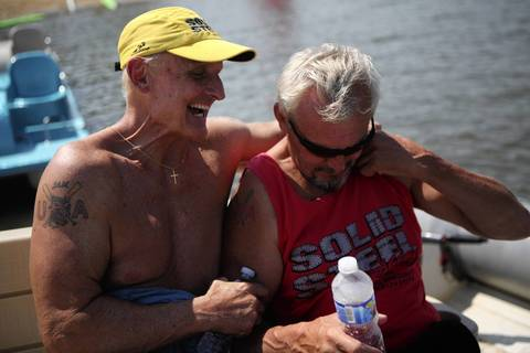Dan Mello, left, and Rod Reiche, members of Dubuque, Iowa Dragon Boat Association, joke during a break from boating practice.