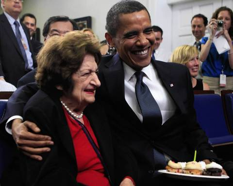 President Barack Obama puts his arm around Hearst White House columnist Helen Thomas after presenting her with cupcakes in honor of her birthday in the James Brady Briefing Room at the White House in Washington in 2009.