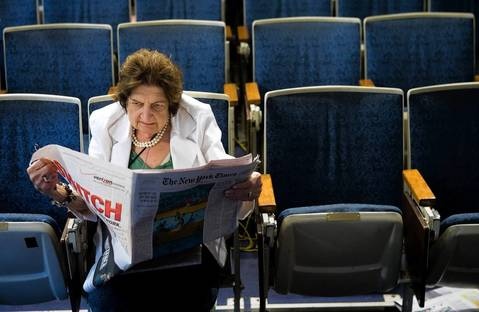 Senior White House Correspondent Helen Thomas reads the newspaper while sitting in her chair in the White House press room in 2006.