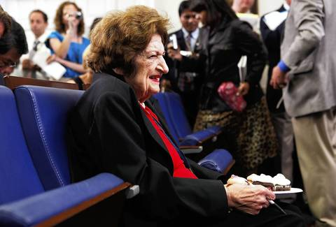 Veteran White House correspondent Helen Thomas holds the birthday cupcakes which were given to her by President Obama to celebrate her birthday in the White House briefing room in 2009.