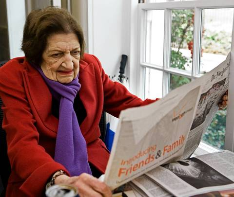 Helen Thomas reads a newspapers at her desk inside the White House briefing room in 2009.