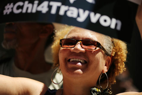 """Regina Davis smiles as she listens to speakers during the """"Justice for Trayvon"""" vigil organized by National Action Network's Chicago Chapter Saturday, July 20, 2013 at the Dirksen Federal Building in Chicago."""