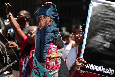 """Maya Samuels, right, listens as her grandmother, Dorothy Burge, holds up a cloth depiction of her great nephew dressed as Trayvon Martin during the """"Justice for Trayvon"""" vigil organized by National Action Network's Chicago Chapter Saturday, July 20, 2013 at the Dirksen Federal Building in Chicago."""