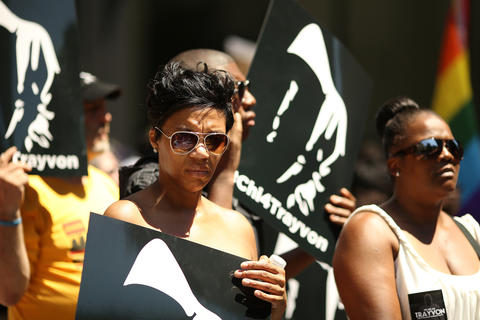"""Takisha Ewings holds a sign as she listened to speakers during the """"Justice for Trayvon"""" vigil organized by National Action Network's Chicago Chapter Saturday, July 20, 2013 at the Dirksen Federal Building in Chicago."""