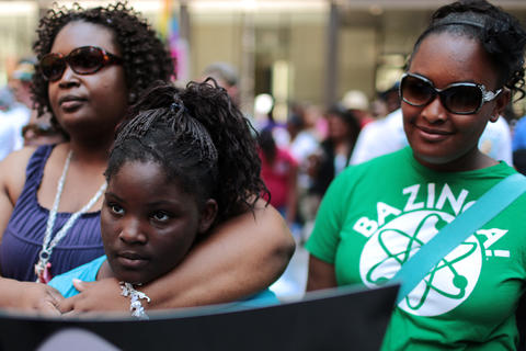"""Jennifer Smith holds her daughter, Cashmere, 10, as they listened during the """"Justice for Trayvon"""" vigil organized by National Action Network's Chicago Chapter Saturday, July 20, 2013 at the Dirksen Federal Building in Chicago."""