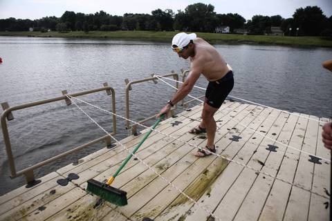 Wojtek Wasilewski, co-captain of Windy City Dragons cleans geese poop on the dock before the team practice.