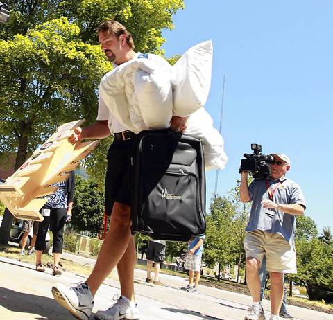 Long snap center Patrick Mannelly has his hands full with personal belongings as he arrives in camp.
