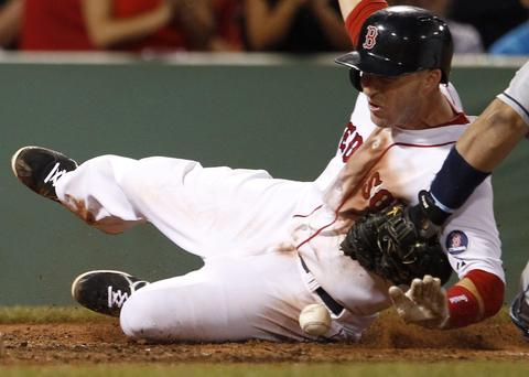 Boston Red Sox Stephen Drew slides home as Tampa Bay Rays catcher Jose Molina loses the ball during their MLB American League Baseball game in Boston, Massachusetts, July 23, 2013.