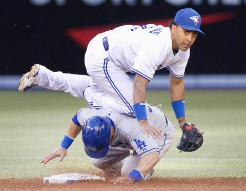 Los Angeles Dodgers' Skip Schumaker is forced out at second base as Toronto Blue Jays' Maicer Izturis turns the double play in the second inning of their Interleague MLB baseball game in Toronto July 24, 2013.