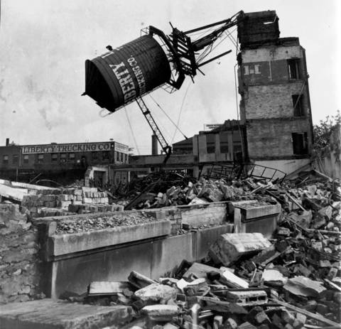A wrecking company topples a water tank at 210 N. Ogden Ave. in Chicago.