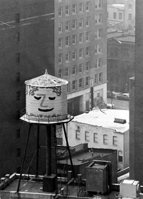With a demure look fresh from the paint bucket, a water tank looks down from the top of the Putman Publishing company building at 111 E. Delaware Place in the mid-1950s.