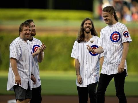 Imagine Dragons, soon to perform at Lollapalooza, throw out the first pitch before the Cubs game against the Dodgers.