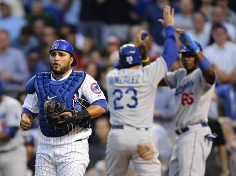 Dodgers Adrian Gonzales celebrates scoring as Cubs catcher Dioner Navarro looks on in the third inning.