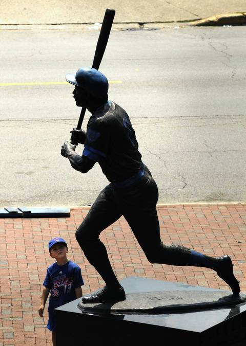 "A young fan stops to look at the statue of ""Sweet Swingin"" Billy Williams near Addison & Sheffield Friday before the game against the Dodgers."