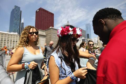 Jenny Kim, 16, of Glenview, makes her way through security as Lollapalooza 2013 kicks off in Chicago's Grant Park Friday.